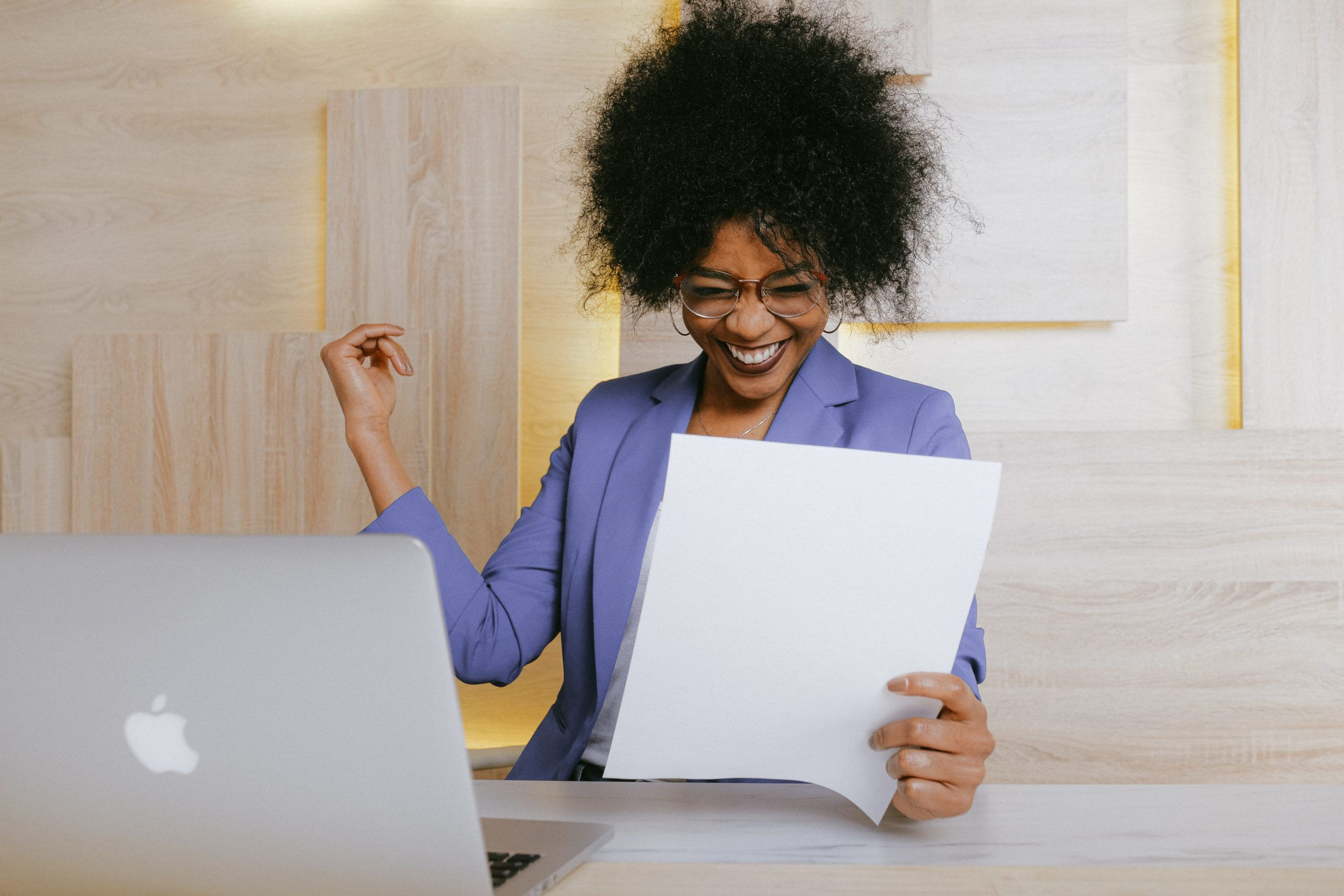 African American woman sitting at her desk, with her Apple computer and papers in hand, expressing joy