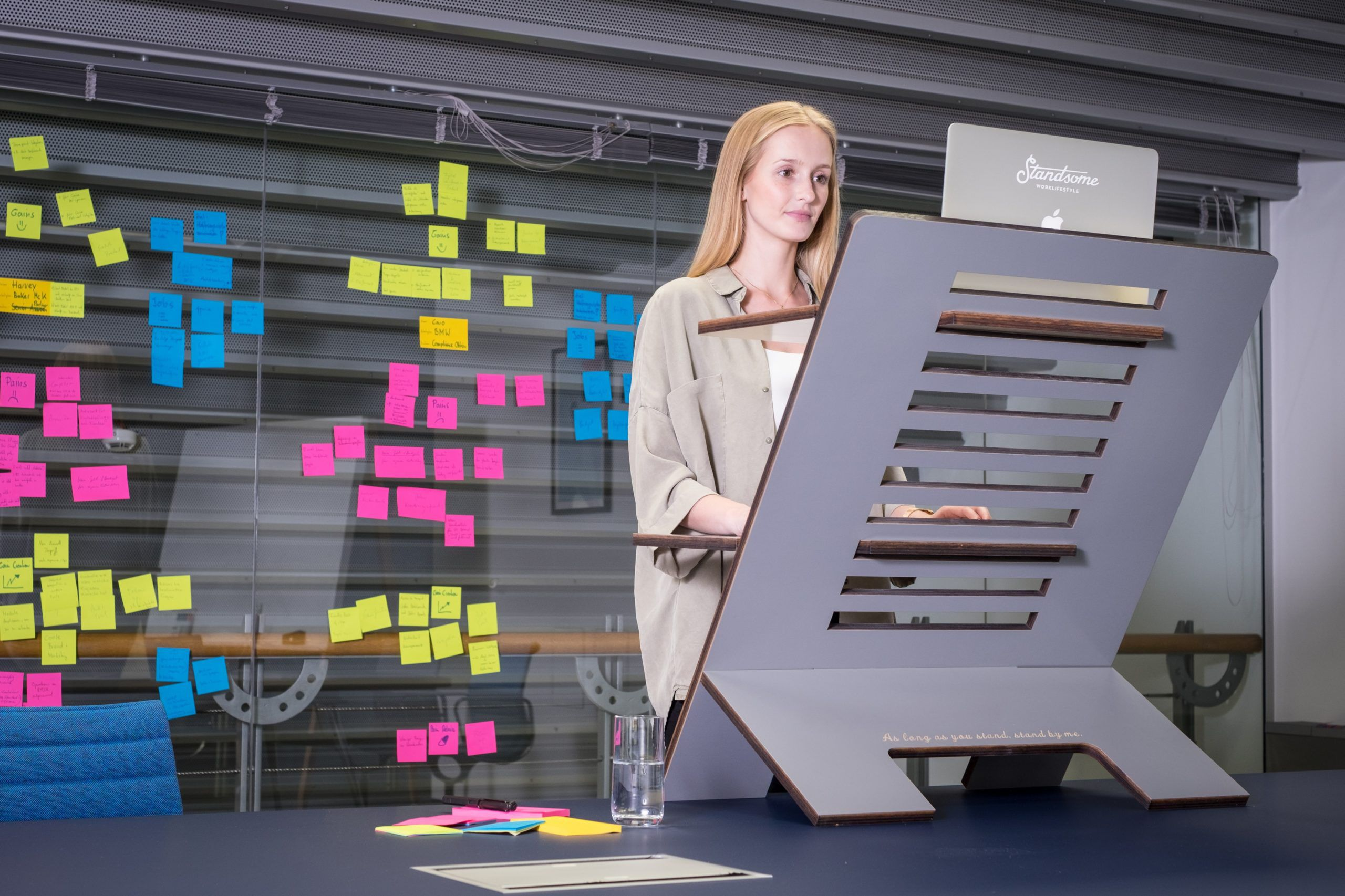 Woman working at a standing desk, with a clear wall of sticky notes behind her