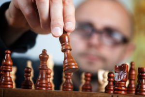 A guy with glasses playing chess, making a chess move