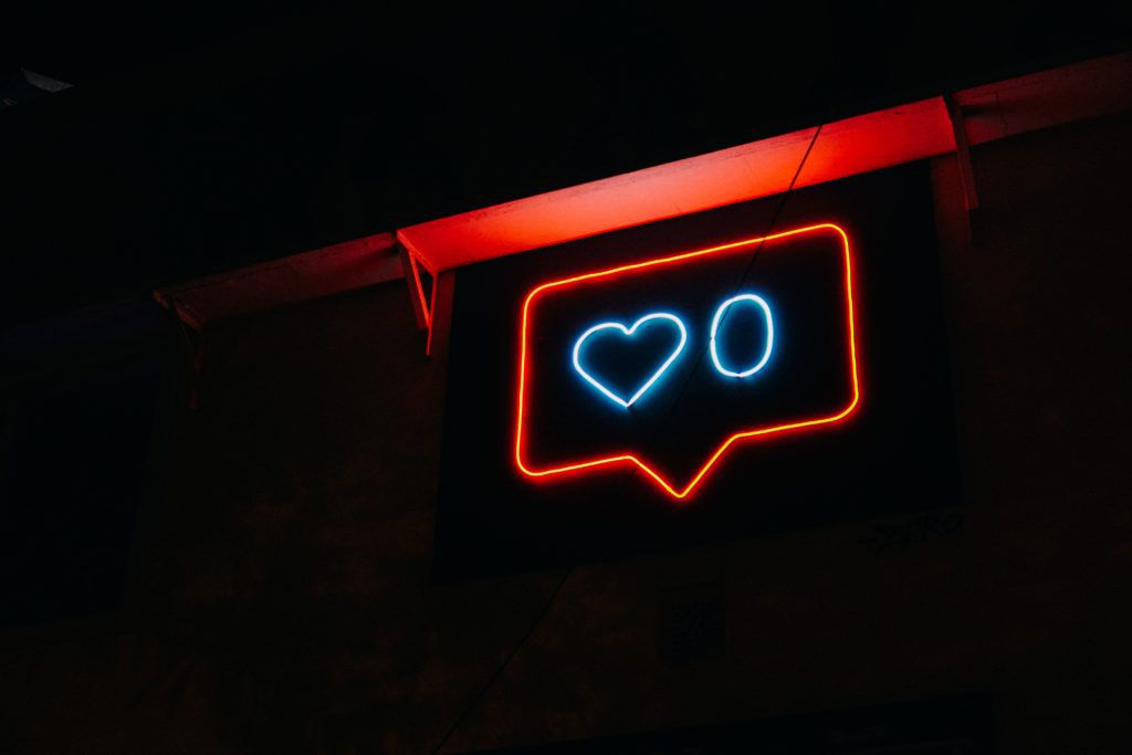 A neon social media like sign in a dimly lit room