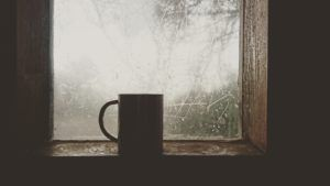 A cup of coffee sitting on a window seal, in front of a window