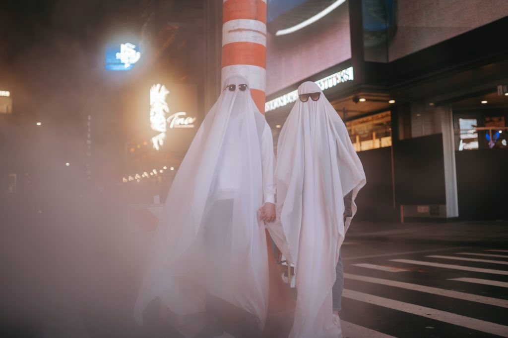 Two people dressed up as ghosts, with sunglass in a busy downtown city